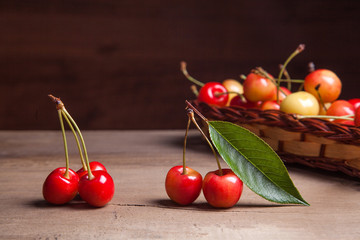 Yellow sweet cherry in basket on wooden background.