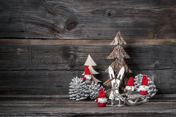 Weihnachtsdeko mit Weihnachtsmännern vor Holzhintergrund
