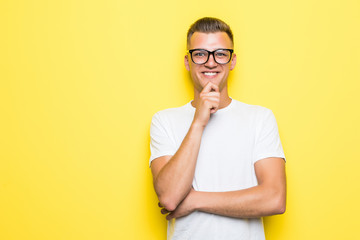 Close up portrait of thoughtful man who looks away touching his chin and weighs the pluses and minuses of the offer isolated on t yellow background