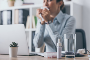 medicines standing on worktable with blurred sneezing businesswoman sitting on background