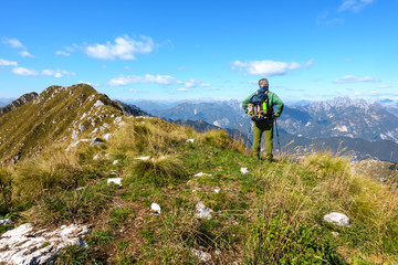 Man hiker on mountain top watching the mountain range.