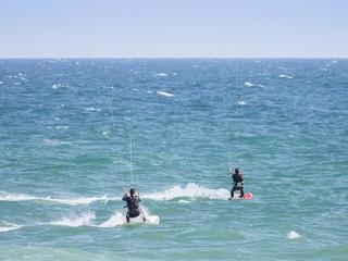 Kite surfers on blue waters of Atlantic Ocean in Portugal