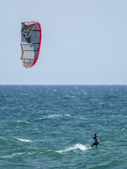 Kite surfer on blue waters of Atlantic Ocean in Portugal