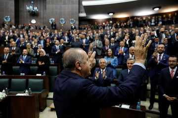 Turkish President Tayyip Erdogan greets members of parliament from his ruling AK Party during a meeting at the Turkish parliament in Ankara