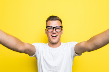 Cheerful man looking at camera and taking selfie on yellow background