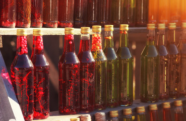 Homemade alcohol drinks in bottles on wooden shelves on outdoor sale. Row of colorful glass bottles with natural drinks.