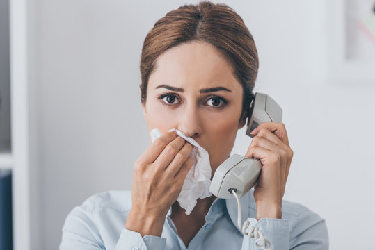close-up portrait of businesswoman with runny nose talking by wired phone and looking at camera