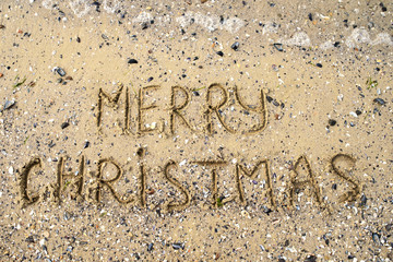 Merry Christmas written on tropical beach sand, copy space. Holiday concept, top view