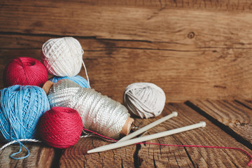 Needlework, macrame, knitting. Yarn and threads of bright colors in a wicker basket on a wooden background. Women's hobby.