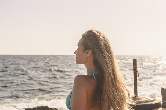 Portrait of a young woman with long hair enjoying the sunshine at sunset by the sea