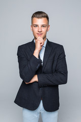 Portrait of a young businessman touching his chin over gray background