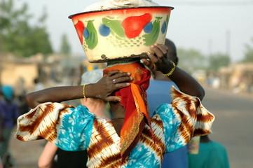 Femme de dos tunique bariolée et bassine colorée sur la tête, Burkina Faso, Afrique