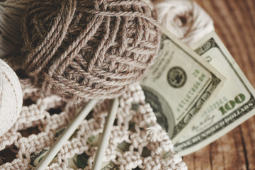 Profitable hobby. Earnings on needlework. Balls of natural color yarn, knitting needles and money on a wooden table.