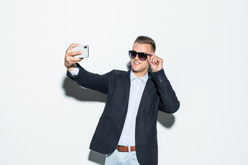 Portrait Handsome Business man take a selfie of himself with smartphone isolated on white background