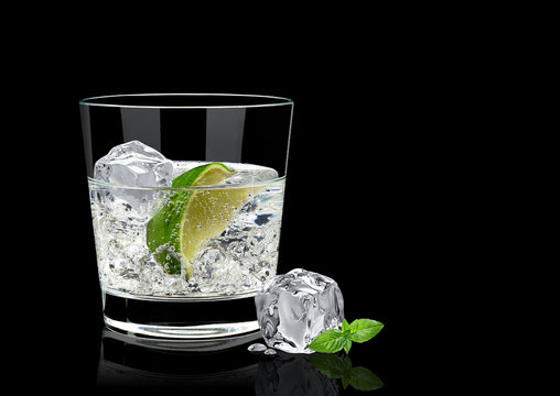 Vodka lime, mojito or gin tonic  with lime wedge and ice in rocks glass on black background including clipping path