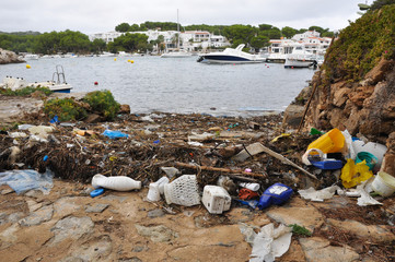 Plastic waste washed up with the sea weed in small cove in Menorca