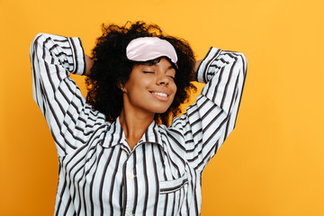 Sleeping. Dreams. Woman portrait. Afro American girl in pajama is stretching and smiling, on a yellow background
