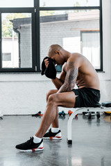 side view of muscular young sportsman wiping forehead with towel while sitting after workout in gym