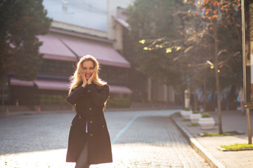 Lifestyle portrait of merry blonde model with lush curly hair posing with sun glare. Space for text