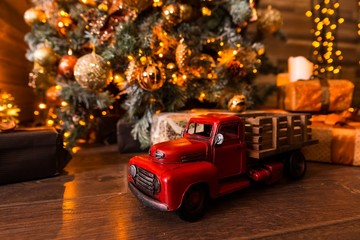 Toy car with a red body is on a wooden floor under the Christmas tree with gifts