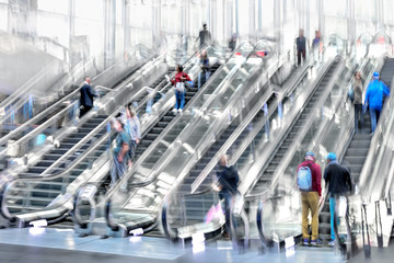 people on moving escalator motion blur
