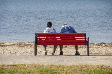 Middle aged couple sitting on a wooden bench near the beach and looking the sea