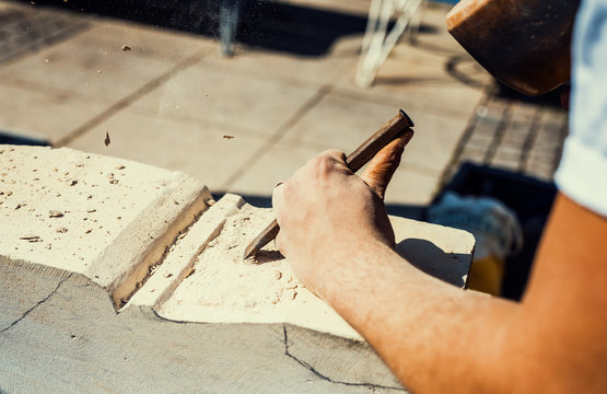 A stonemason is working on a sandstone block with chisel and hammer