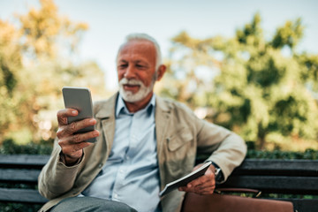 Smiling senior man using mobile phone while sitting on the bench.