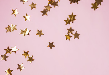 Golden shiny decorative stars on the pink background, top view.