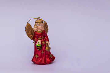 Christmas tree angel figure with red dress and golden wings on white background