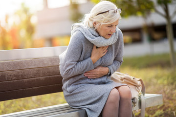 Senior Woman Suffering From Chest Pain While Sitting On Bench