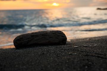 sunset at sea, bottom view, large dark sand, wooden piece ice next
