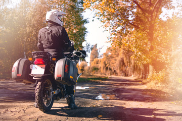 Motorbiker travelling, autumn day, motorcycle off road, rider, adventurer, extreme tourism, cold weather clothes, yellow forest, copy space, light tinting