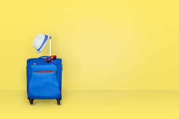 Blue suitcase with a summer hat and fashionable  sunglasses on light yellow background, a summer vacation travel concept, free space with a place for copying.