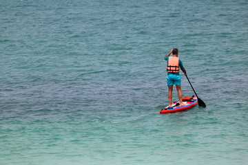 Tourist man enjoying the stand up paddle board or surfboard on the tropical beach