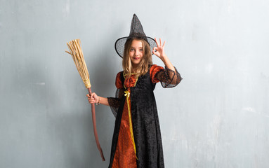 Little girl dressed as a witch and holding a broom for halloween holidays making OK sign