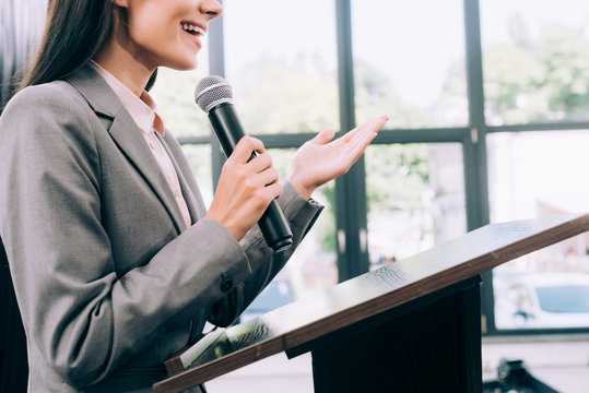 cropped image of smiling lecturer talking into microphone and gesturing at podium tribune during seminar in conference hall