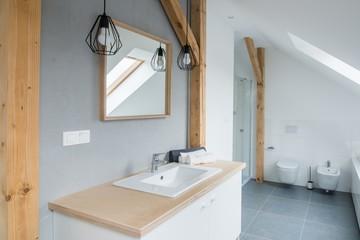 Bright modern bathroom with grey walls, mirror and bathtub.