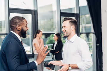 smiling multicultural businessmen having conversation in conference hall