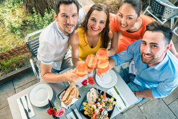High-angle view portrait of four cheerful and beautiful young friends, looking at camera while toasting at a trendy restaurant with delicious food outdoors in summer