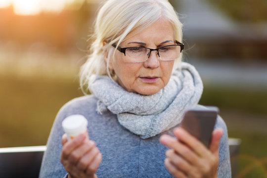 Woman holding smartphone and pill bottle