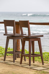 Wooden chairs and table in empty cafe next to the sea on the tropical beach, Sri Lanka. Close up
