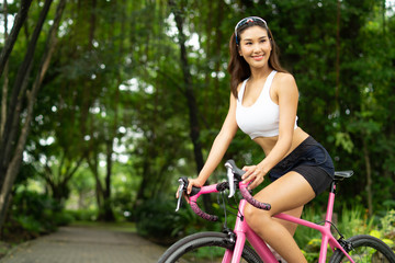 Smiley beautiful sport woman riding pink bicycle in the park