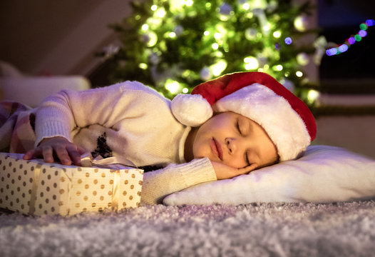 little girl  sleeping under Christmas tree