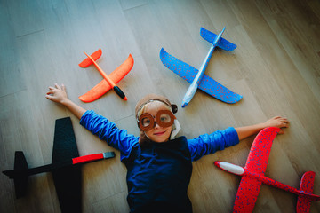 happy little boy with helmet and glasses play with toy planes