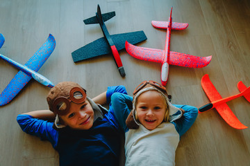 little pilots- happy kids with helmet and glasses play with toy planes