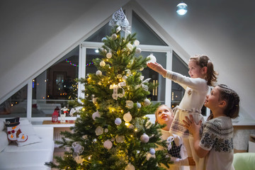 girls  decorates a Christmas tree