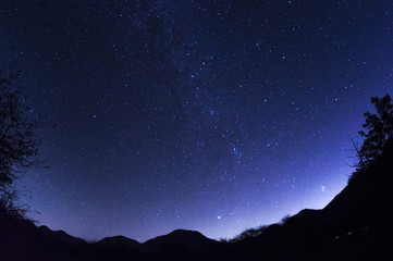 魚眼レンズで撮影した山の上に注ぐ星空