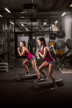 Two attractive women exercising on stepper in gym. Healthy lifestyle concept.