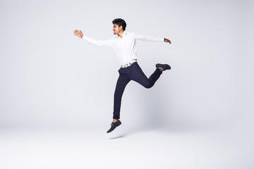 Full length of young indian man cheering and jumping isolated over white background